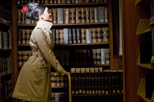 Stock Photo: 1742R-19865 Cheerless young woman sitting in library by bookshelf