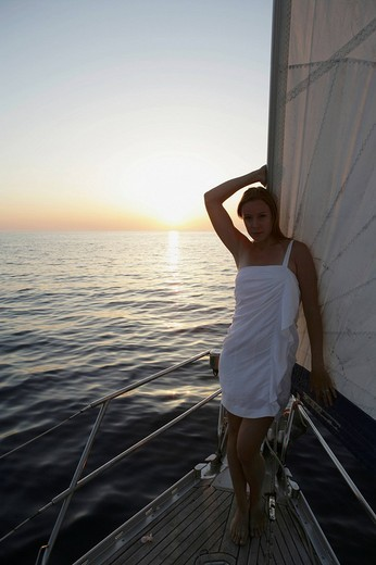 Stock Photo: 1742R-20063 A thoughtful young woman leaning on sail in a boat