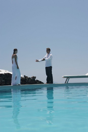 Young couple about to embrace on poolside by swimming pool : Stock Photo