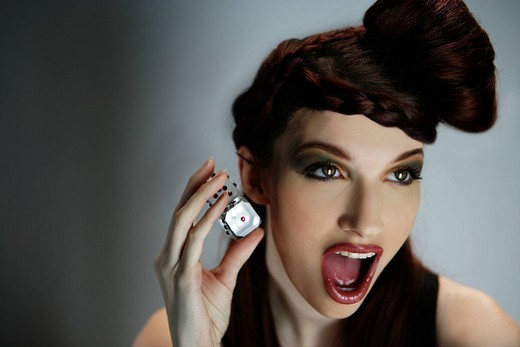 Portrait of excited stylish woman with retro hairstyle holding dice, studio shot : Stock Photo