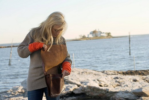 Stock Photo: 1742R-20817 Portrait of stylish young woman in grey sweater standing in coastal landscape
