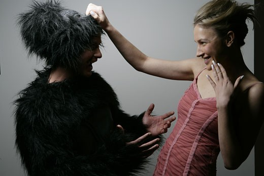 A woman is holding on to a gorilla mask. : Stock Photo