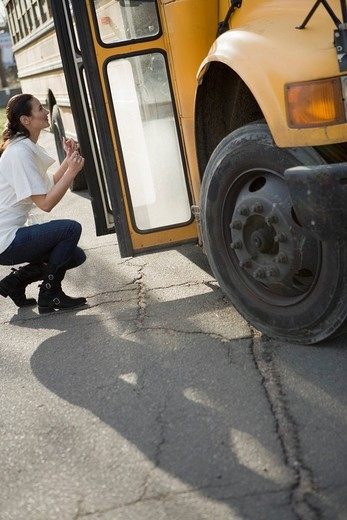 Side view of a young woman crouching by bus door : Stock Photo