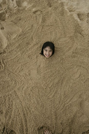 A small girl is buried in sand. : Stock Photo