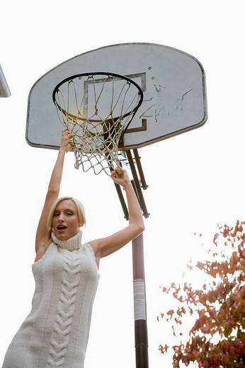 Portrait of young blonde woman hanging from basketball hoop : Stock Photo