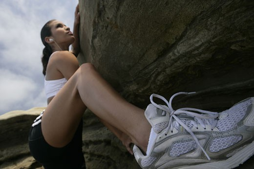 Stock Photo: 1742R-2420 View of a woman climbing up a cliff.