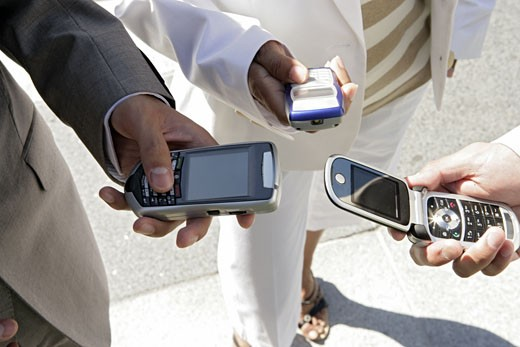 Stock Photo: 1742R-2551 Three people are holding their cellphones.
