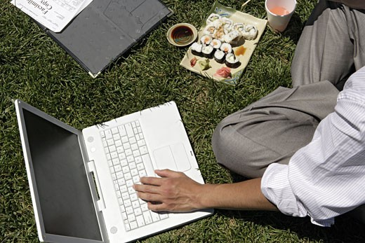 Stock Photo: 1742R-2565 An executive is working on his laptop during lunch.