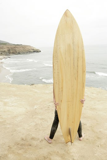 View of a person hidden with a surfboard. : Stock Photo