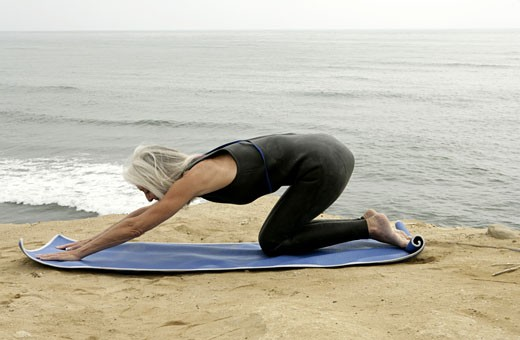 View of a woman stretching out near a sea. : Stock Photo