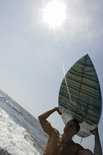 View of a young man carrying a surfboard. : Stock Photo