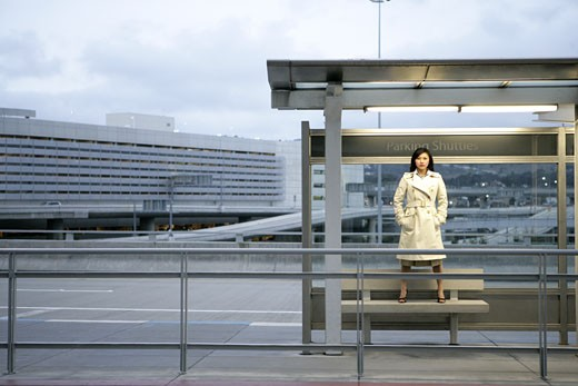 A woman is standing on a bench under a shelter. : Stock Photo