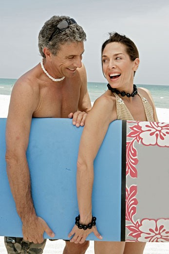 Stock Photo: 1742R-3704 Couple carrying a surfboard on beach.