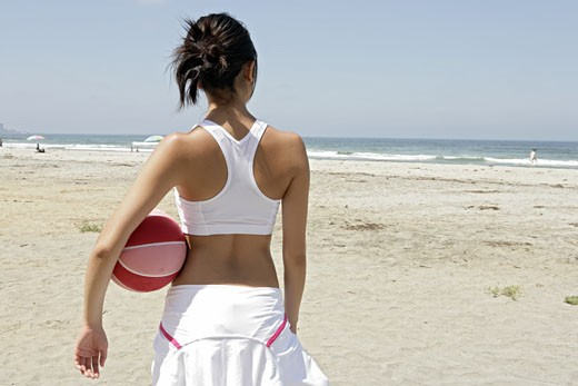 A woman is holding a rubber ball and standing on a beach. : Stock Photo