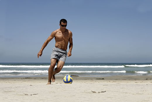 A young man is playing on the beach. : Stock Photo
