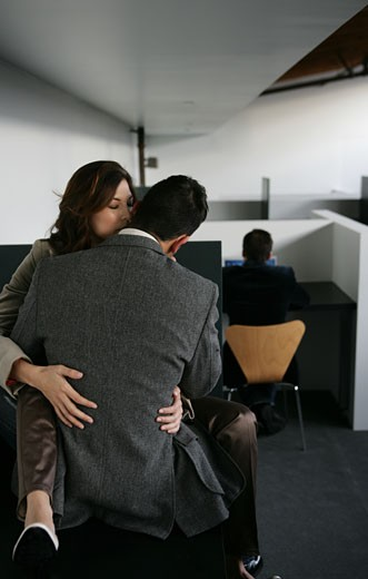 Couple embracing in the office behind a co-worker : Stock Photo