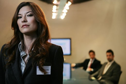 Three people inside a conference room, woman standing apart : Stock Photo