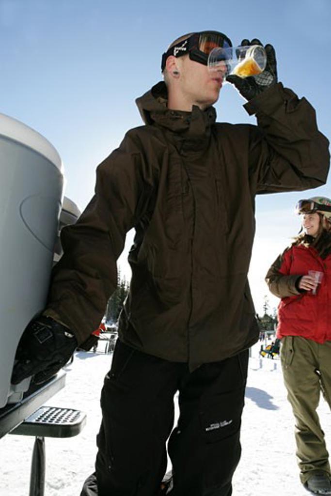 Man drinking on a ski slope : Stock Photo