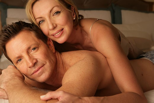Mature couple in bedding smiling : Stock Photo