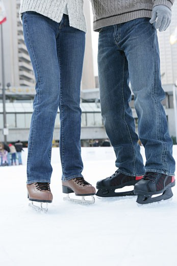 Man and a woman wearing jeans and ice skates : Stock Photo