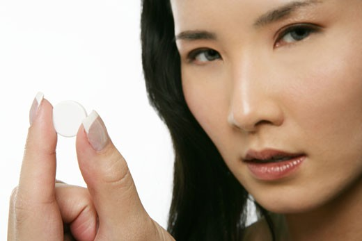 Asian woman holding a pill, looking at camera : Stock Photo