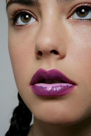 Portrait of Caucasian woman with dripping lip gloss : Stock Photo