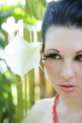 Woman's face with a large flower in her  hair : Stock Photo