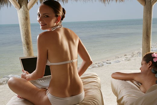Young women getting massages at beach and using laptop. : Stock Photo