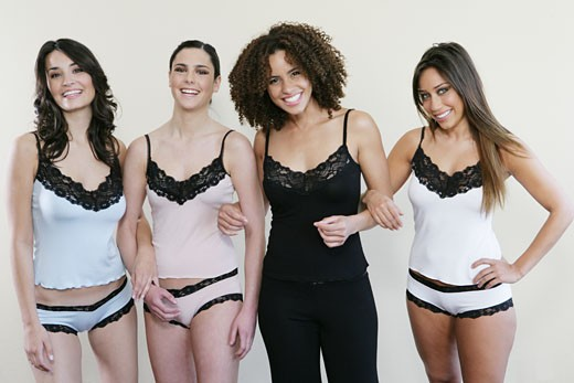 Stock Photo: 1742R-6304 Four women in lingerie arm in arm, looking at camera