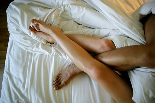 Stock Photo: 1742R-6457 Detail of couple's legs intertwined in bed.