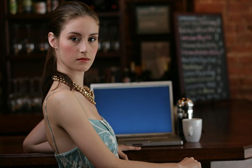 Young woman sitting at bar with laptop. : Stock Photo
