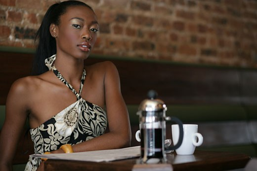 Stock Photo: 1742R-6658 Young stylish African-American woman sitting in cafe.
