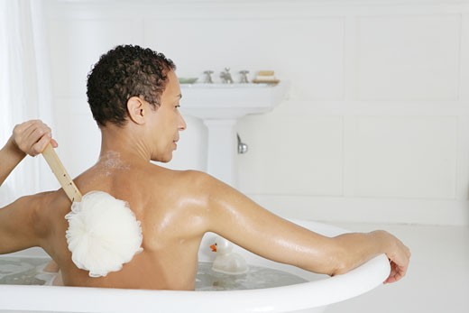 Stock Photo: 1742R-7219 African American woman scrubbing her back in bathtub.