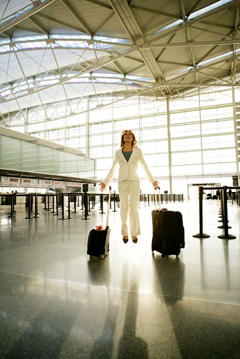 Young businesswoman levitating in airport. : Stock Photo