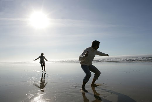 Young couple skipping rocks at beach. : Stock Photo