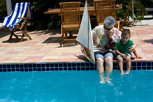 Senior woman holding a sailboat with her grandson at poolside : Stock Photo
