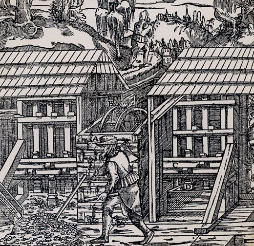 Stamping mills powered by and overshot water wheel being used to crush ore to begin the process of extracting metal from the ore won from a mine.   From De re metallica, by Agricola, pseudonym of Georg Bauer (Basle, 1556).  Woodcut : Stock Photo