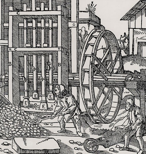 Overshot water wheel turning the cam-shaft of a stamping mill  being used to turn the crush ore to begin the process of extracting metal from the ore won from a mine.  From De re metallica, by Agricola, pseudonym of Georg Bauer (Basle, 1556).  Woodcut : Stock Photo