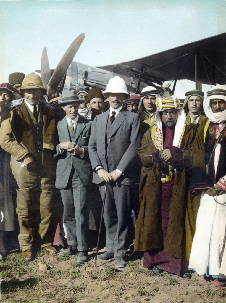 Stock Photo: 1746-3639 On the airfield at Amman,  Jordan, April 1921:  T E Lawrence,  Sir Herbert Samuel (British High Commissioner of Palestine), Emir Abdullah. Woman far left, possibly Gertrude Bell. Sheik Majid Pasha el Adwan, far right.