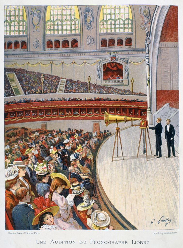 Stock Photo: 1746-4490 Demonstration on the stage of a crowded auditorium of Henri Lioret's weight-driven cylinder phonograph mounted on a tripod, c1898.  Sound Recording Technology Invention