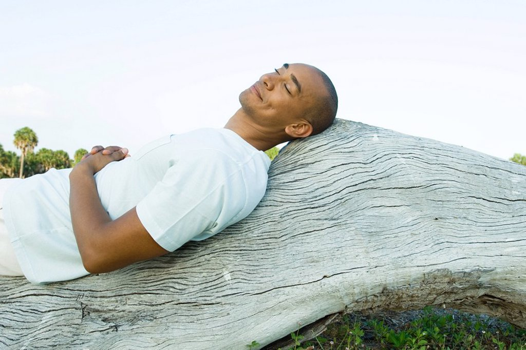 Man lying on back on wood surface, eyes closed, smiling : Stock Photo