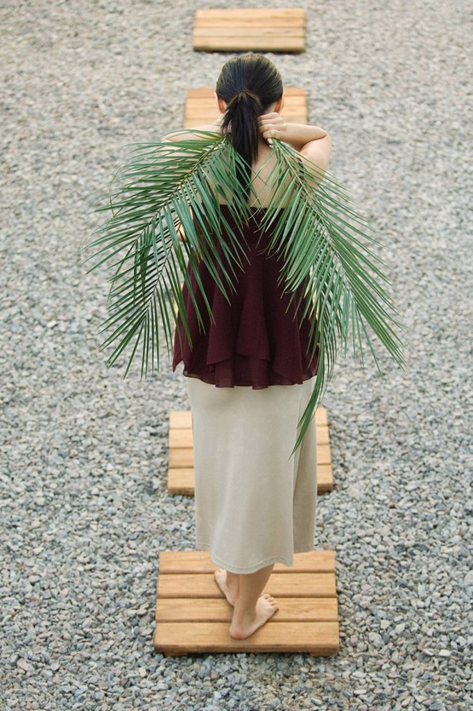 Woman standing on foothpath, carrying palm leaves behind back, rear view : Stock Photo