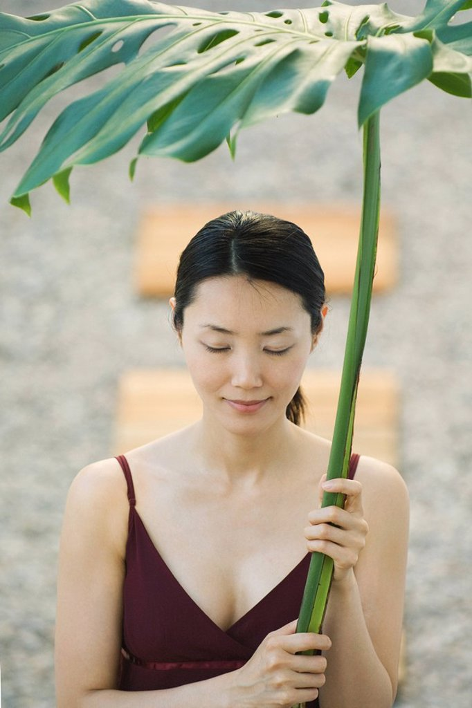 Woman holding palm leaf over her head, eyes closed, smiling : Stock Photo