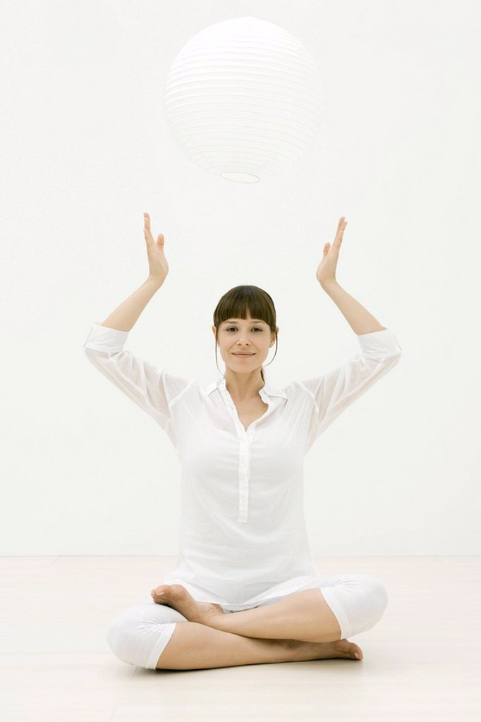 Stock Photo: 1747R-10373 Woman meditating with sphere over head