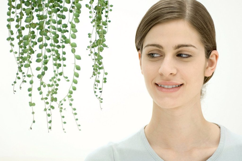 Young woman in front of hanging plant : Stock Photo