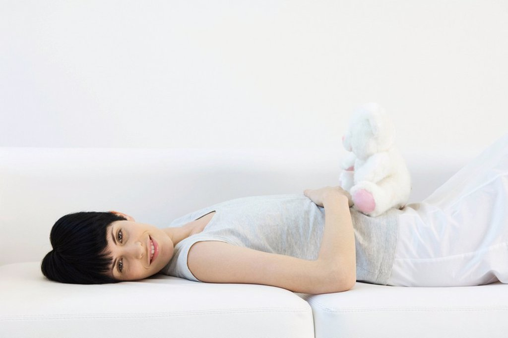 Stock Photo: 1747R-10416 Woman lying on back on sofa, teddy bear sitting on her stomach, smiling at camera