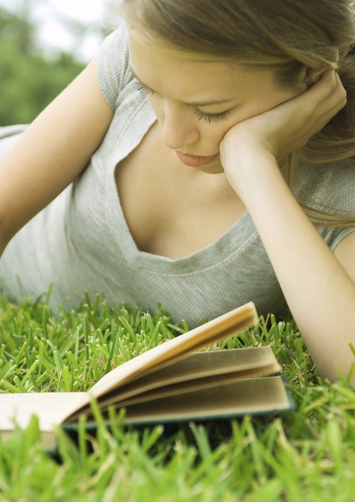 Young woman reclining in grass with book : Stock Photo