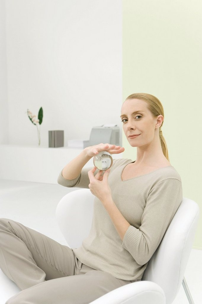Professional woman holding crystal ball, smiling at camera : Stock Photo