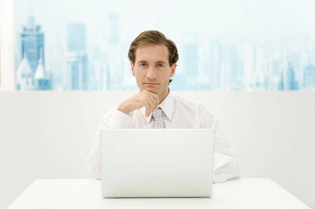 Businessman sitting in front of laptop computer, hand under chin, looking at camera : Stock Photo