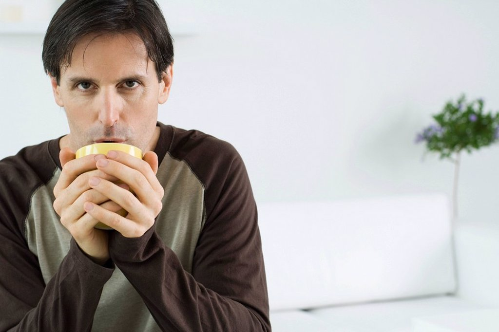 Man holding cup with both hands, blowing into cup, looking at camera : Stock Photo
